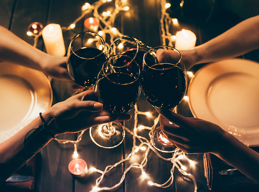 Four people clinking glasses with wine